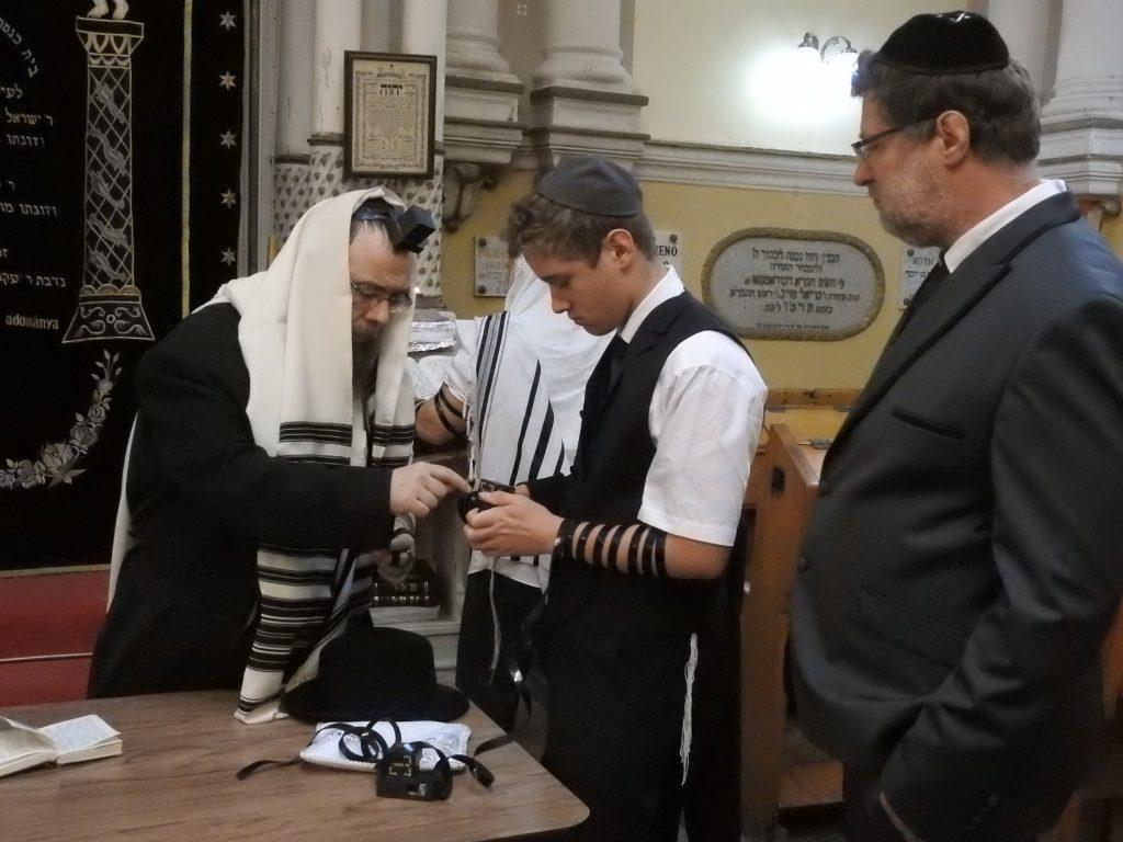 Édesapja figyeli Iimit, amint Tfilint rak Báruch rabbi segítségével.